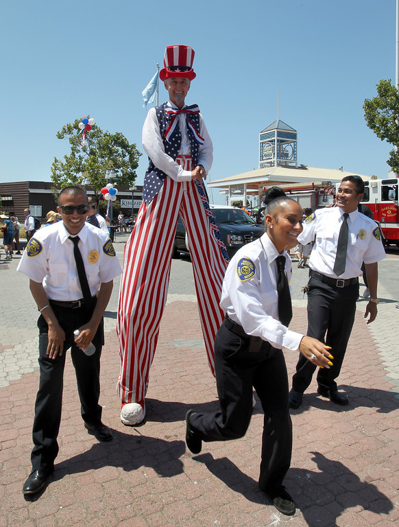 . Security guards just finished having their picture taken with Drew Letchworth, of El Cerrito, as Uncle Sam on stilts as they celebrate Independence Day at Jack London Square in Oakland, Calif., on Thursday, July 4, 2013.  (Ray Chavez/Bay Area News Group)