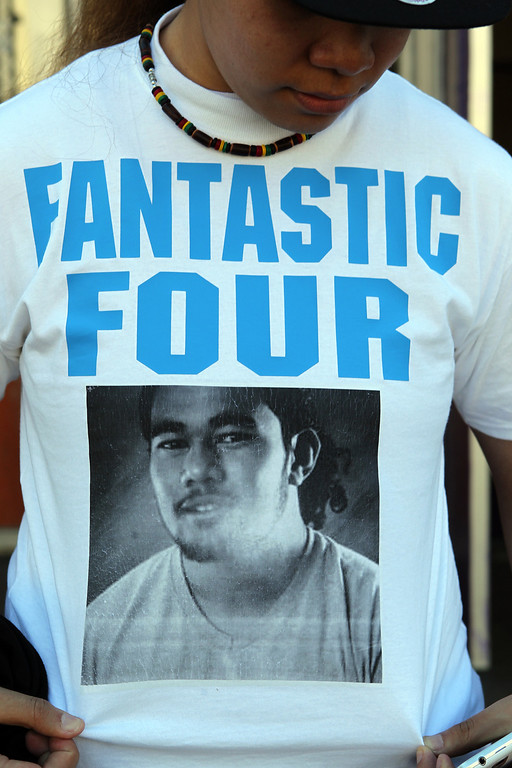 . Vi Fatai, 23, a cousin of four teens George Moa, 19, David Moa, 19, Malia Moa, 19, and Rachel Fisi\'iahi, 17, who all died in a car accident wears a memorial t-shirt with a photo of David Moa, 19, outside Castlemont High School in Oakland, Calif., on Thursday, Feb. 14, 2013. Family, friends, classmates and staff attended a memorial service at the school for the four teens. (Anda Chu/Staff)