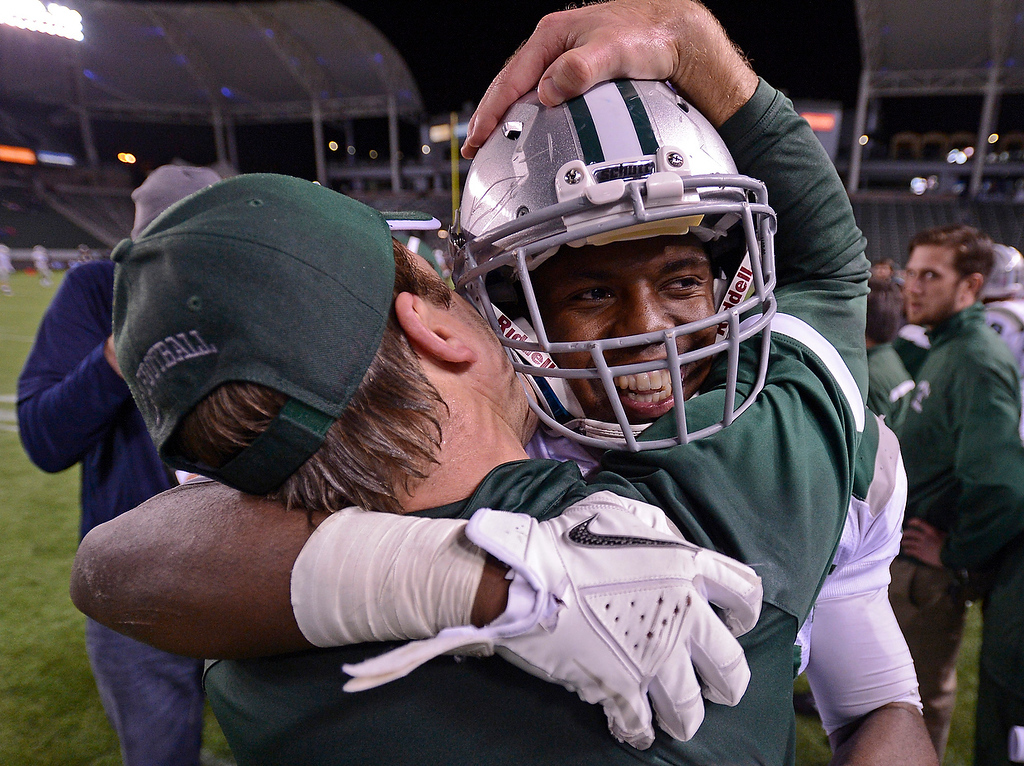 . De La Salle Spartans\' assistant coach Justin Alumbaugh hugs player Michael Hutchings (17) in the final minute of the fourth quarter of the Centennial Huskies in the Open Division during the 2012 CIF State Football Championship at Home Depot Center in Carson , Calif. on Saturday, Dec. 15, 2012. De La Salle defeated Centennial 48-28. (Jose Carlos Fajardo/Staff)