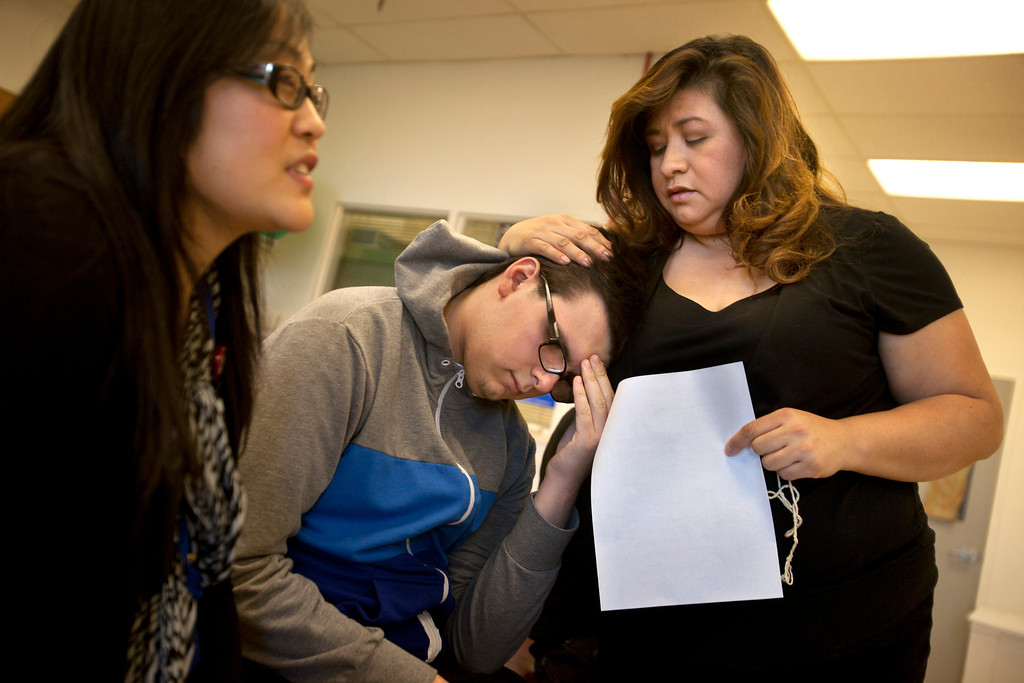 ". Everett Zamarron-Smith is comforted by his mother, Delva, after getting a headache while undergoing physical therapy with therapist Annie Orozco, left, at the Valley Medical Center rehabilitation center in San Jose Thursday, Jan. 3, 2013. When Everett Zamarron-Smith tumbled off his skateboard last June, everything changed. The 16-year-old Gilroy High School student suffered a traumatic brain injury and today is making slow progress in the arduous process of reclaiming his life. While it only was recently that Everett began to understand what happened to him, and why he finds himself in a wheelchair, his mother Delva Zamarron describes the last seven months this way: ""You wonder if this is really happening.\"" (Patrick Tehan/Staff)"
