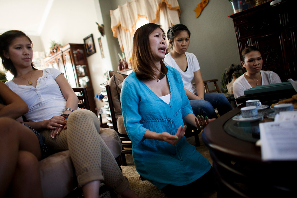 . Jennie-Diem Nguyen, center, is overwhelmed with emotion as she and her sisters, Joanne, (not pictured) Dalena, left, Dee, center right, and Sharon, right, recount the death of their brother, Vince Canh Xuan Nguyen, to this newspaper on July, 16, 2013 at their mother\'s San Jose home.  The San Jose family believes there may be foul play behind the death of Vince Canh Xuan Nguyen, shown in a photo at right, who passed away in a tiny hotel room in Vietnam on July 1, 2013, after a night of drinking ended with him gravely ill, unable to control his body functions. (Dai Sugano/Bay Area News Group)