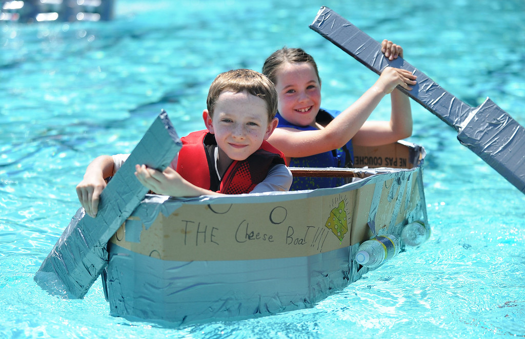""". Toby Radding, left, and his sister Taylor Radding, 8, of Lafayette, paddle across a pool in their watercraft named \""""The Cheese Boat!!!\"""" made of only cardboard, recyclables and duct tape during the Derby Day boat race held at Pleasant Hill Aquatic Park in Pleasant Hill, Calif., on Friday, July 19, 2013. (Doug Duran/Bay Area News Group)"""