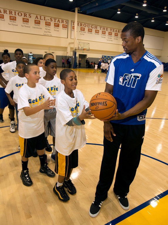 . Golden State Warriors forward Harrison Barnes, left, demonstrates the proper shooting technique to a group of children participating in a basketball clinic at the Warriors practice facility in downtown Oakland, Calif., Wednesday, Jan. 30, 2013. The Warriors and Kaiser Permanente hosted the event as part of the NBA FIT Live Healthy Week. (D. Ross Cameron/Staff)