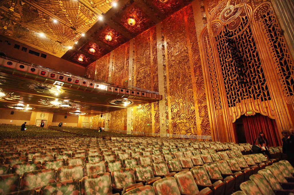 . Floor-to-ceiling murals in a golden relief frame the interior of the Paramount Theatre in Oakland. Before the theater was renovated in the early 1970s, the golden walls were covered by layers of black smoke. (Laura A. Oda/Bay Area News Group)