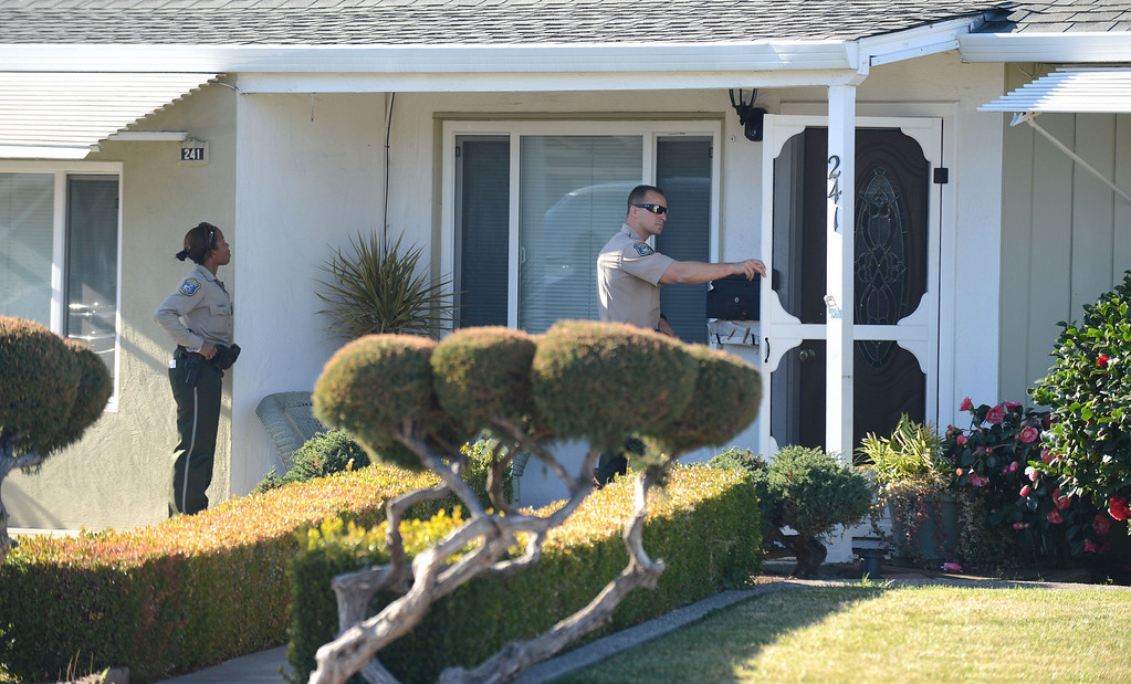 . Santa Clara County Sheriff\'s Deputy Ryan Griep, right, knocks on the door of a home as Deputy Dessaure (she did not want her first name used), left, keeps watch in an unincorporated portion of East San Jose, Calif. on Monday, Feb. 11, 2013. The Santa Clara County Sheriff\'s Office is increasing its efforts to take once lawfully owned firearms from those who can no longer own them due to more recent circumstances in their lives. Officers are attempting to make contact with these people to ask them to voluntarily turn over any firearms. The person they were looking for at this home was deceased. A monthly list of these people is put out by the Department of Justice. (Dan Honda/Staff)