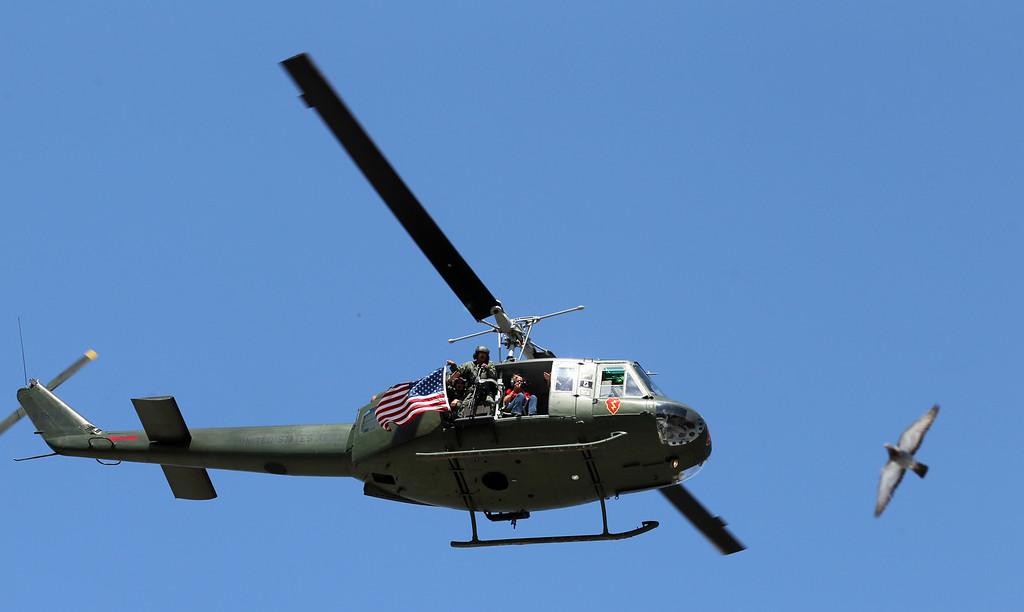 . A military helicopter hovers above the Alameda Mayor\'s July 4th Parade on Park Street in Alameda, Calif., on Thursday, July 4, 2013. (Ray Chavez/Bay Area News Group)