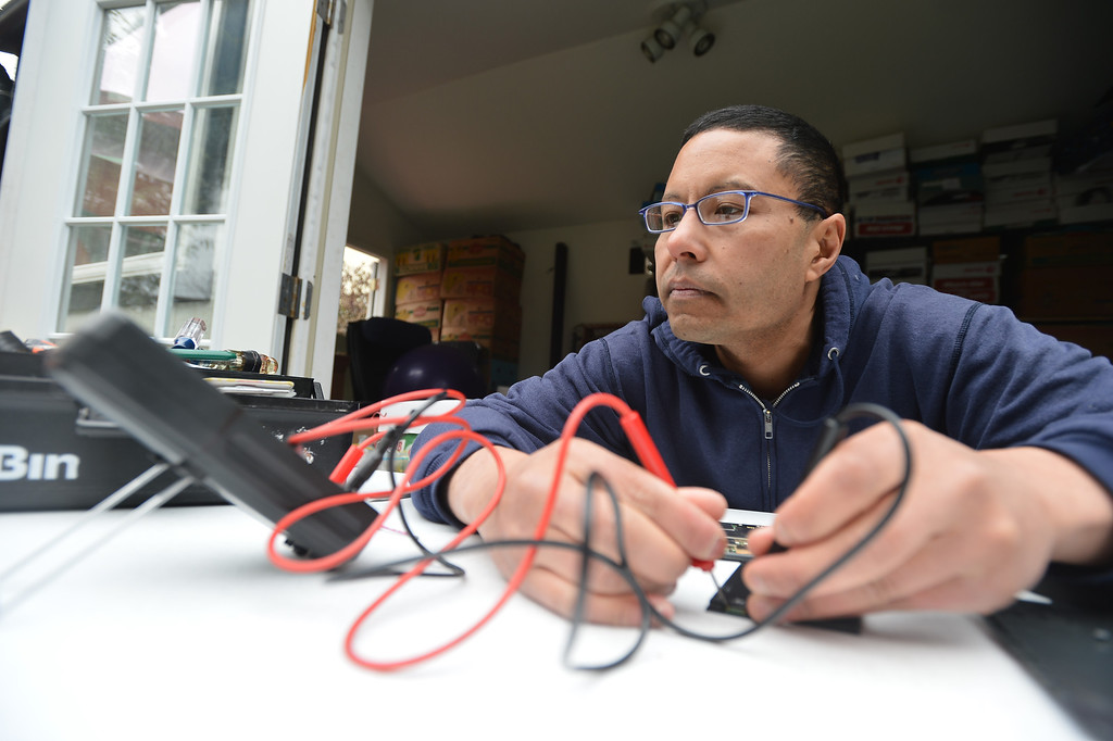""". Peter Mui tests the battery voltage of a Kindle at his home in Berkeley, Calif. on Tuesday, Feb. 5, 2013. Mui learned that the Kindle has a malfunctioning battery and might be repairable. Mui and others run \""""Fixit Clinics,\"""" where they assist people in the repair of various electrical appliances, from televisions to toasters. (Kristopher Skinner/Staff)"""