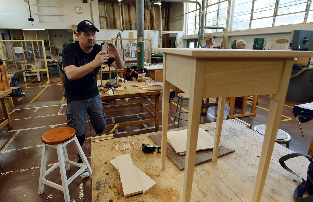 . Noah Bailey takes pictures of his Shaker table in Pleasant Hill, Calif. on Wednesday, July 24, 2013. The Diablo Woodworkers are reaching out to military veterans like Bailey and emphasizing the therapeutic qualities of woodworking. (Kristopher Skinner/Bay Area News Group)