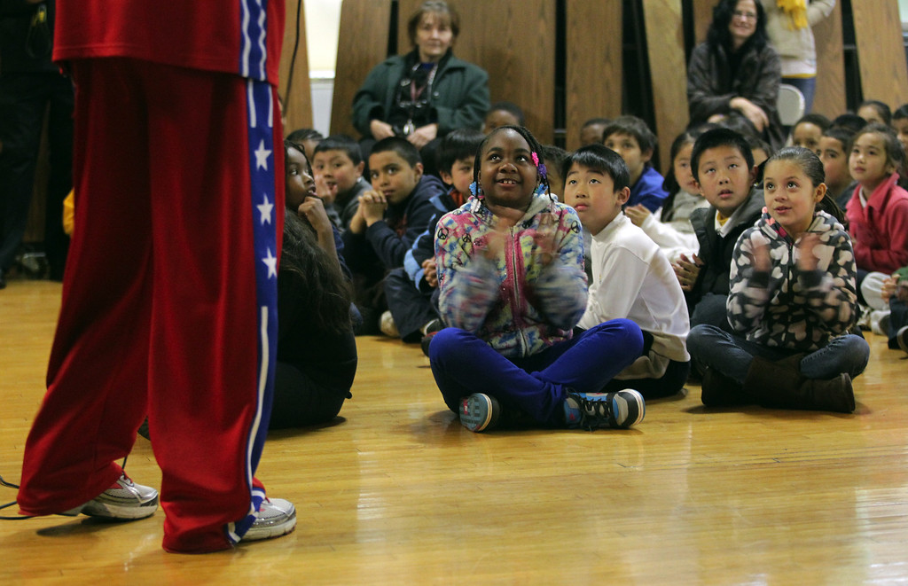 . Students listen to Harlem Globetrotters� Slick Willie Shaw during a visit to Laurel Elementary School in Oakland, Calif., on Wednesday, Jan. 16, 2013. (Anda Chu/Staff)