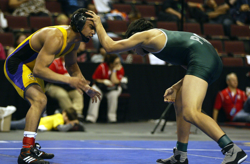 . Riordan\'s Zac Contreras, left, wrestles Poway\'s Victor Lopez in a 145-pound third place match during the California Interscholastic Federation wrestling championships in Bakersfield, Calif., on Saturday, March 2, 2013. Lopez would go onto win the match. (Anda Chu/Staff)