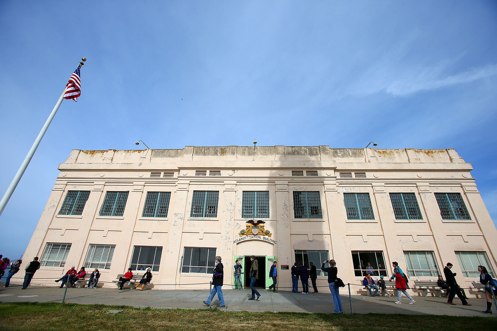 . Tourists walk past the administraion building for the federal penitentiary on Alcatraz Island on Monday, March 18, 2013 in San Francisco, Calif.   The federal prison on the island closed 50 years ago and is now a tourist destination.  (Aric Crabb/Staff)