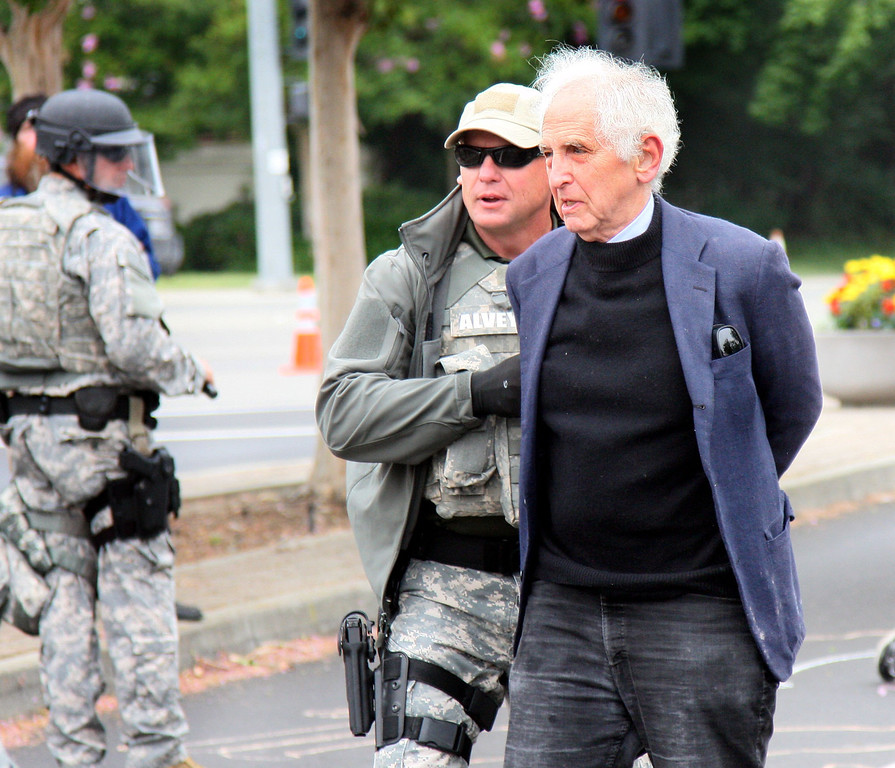. Daniel Ellsberg is arrested in Livermore, Calif., on Tuesday, Aug. 6, 2013, by an officer from Lawrence Livermore Laboratory\'s protective forces at a protest of nuclear weapons at the lab on the 68th anniversary of the atomic bombings of Hiroshima and Nagasaki during WWII.  (Jim Stevens/Bay Area News Group)