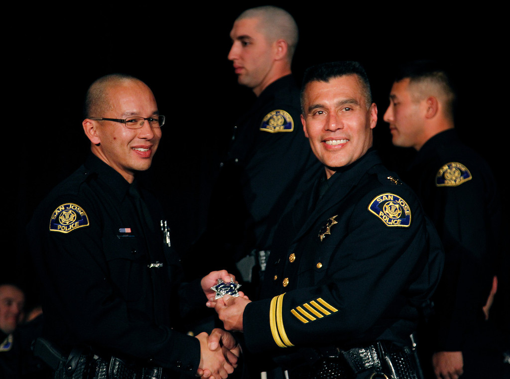 . At left, San Jose Police Department Recruit Officer Alex Ribeiro receives his badge from Chief of Police Larry Esquivel, right,  at the San Jose Police Academy graduation in San Jose, Calif. on Friday, March 15, 2013.   (LiPo Ching/Staff)