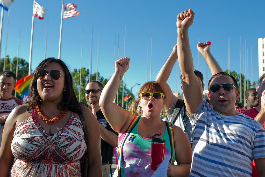 . From left, Monica Gimenez, Jen Behler and Roman Fernando cheer at a San Jose City Hall rally to celebrate the U.S. Supreme Court decision on DOMA and Proposition 8, in San Jose, Calif. on Wednesday, June 26, 2013. (LiPo Ching/Bay Area News Group)