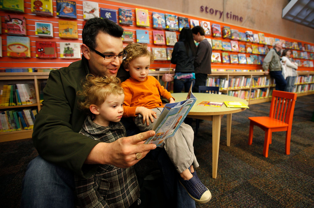 . Adam Corkins of San Jose reads to his children, Lucia, 20 months and Gus, 3, on opening day of the new Bascom Branch Library in San Jose Saurday, Feb. 23, 2013.  The 20,000 sq. ft. library features a living room with a fireplace,Tech Center, Group Study Rooms, a large Quiet Study Room, Teen Room, and a Family Learning Center. Public art at the library features artwork by artist Ron Baron titled �Stratigraphy.�  This is one of the four libraries that were delayed opening because of budget problems.  (Patrick Tehan/Staff)
