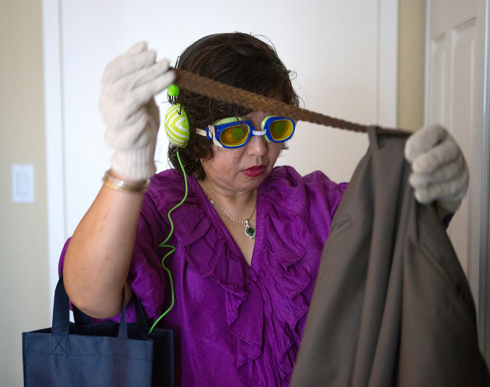 . Angelita Villanueva, whose father has dementia, tries to thread a belt through a pair of pants as she takes the virtual dementia tour at Atria Burlingame, in Burlingame, Calif. on Saturday, Feb. 9, 2013. The four minute tour which caregivers wear distorted goggles and bulky gloves while performing everyday tasks, giving them a sense the sensory challenges people with dementia face. (John Green/Staff)