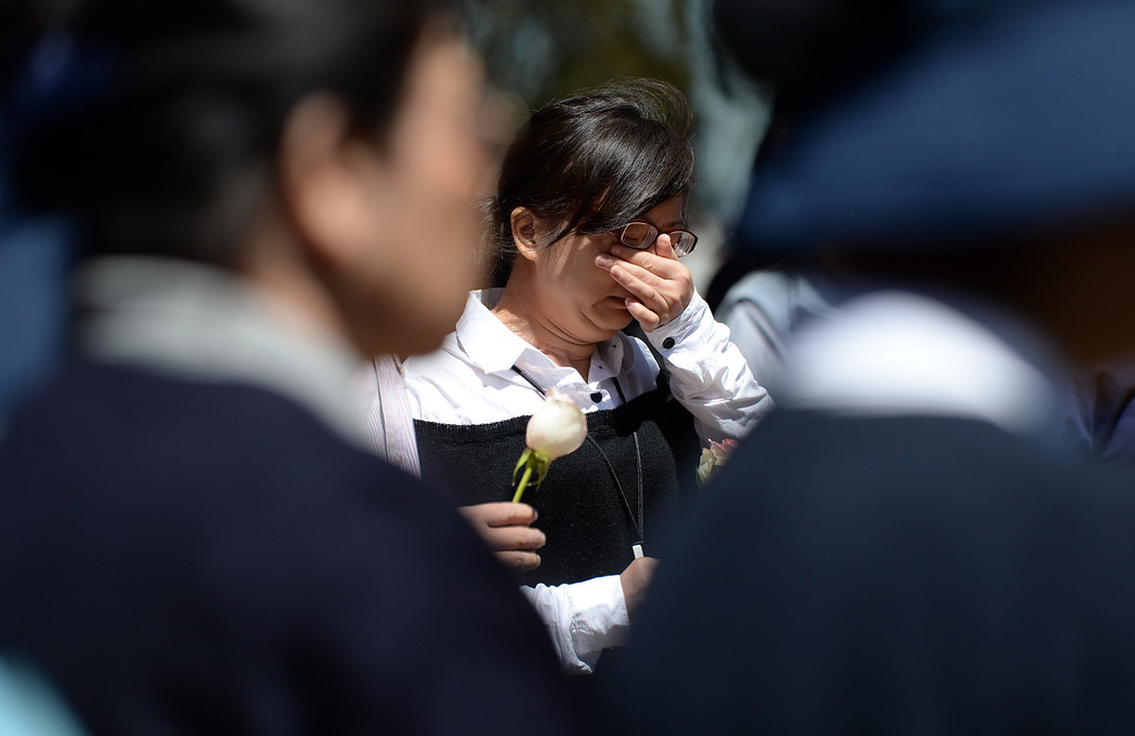 . A woman identified as the mother of Asiana crash victim Ye Mengyuan wipes away tears during a prayer ceremony for the Asiana Flight victims put on by the Tzu Chi Foundation in Burlingame, Calif., on Saturday, July 13, 2013. Tzu Chi is an international Buddhist relief organization that began in Taiwan and offers compassionate efforts for charity, medical treatment, education and disaster relief.  (Dan Honda/Bay Area News Group)