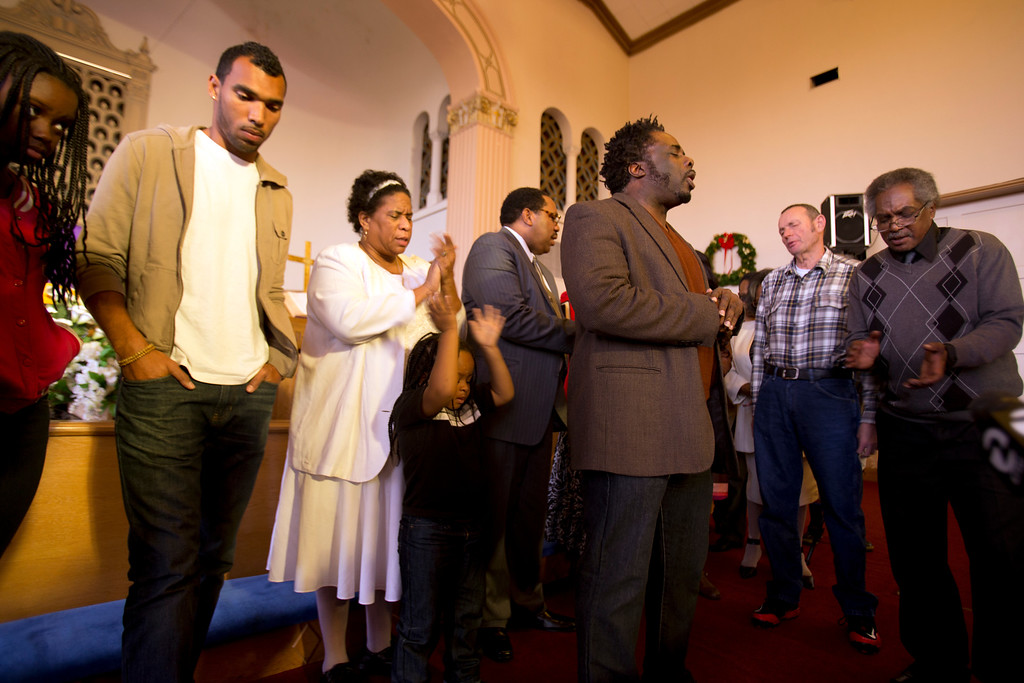 . Rev. Derrick Mann, of Yeshua Ministries in Hayward, center, leads a prayer for 13-year-old Jahi McMath on Sunday, Dec. 29, 2013, at Church of All Faiths in Oakland, Calif. Mann announced that a planned fundraiser to pay for moving the brain-dead McMath from Childrens Hospital Oakland to another medical facility was cancelled. (D. Ross Cameron/Bay Area News Group)