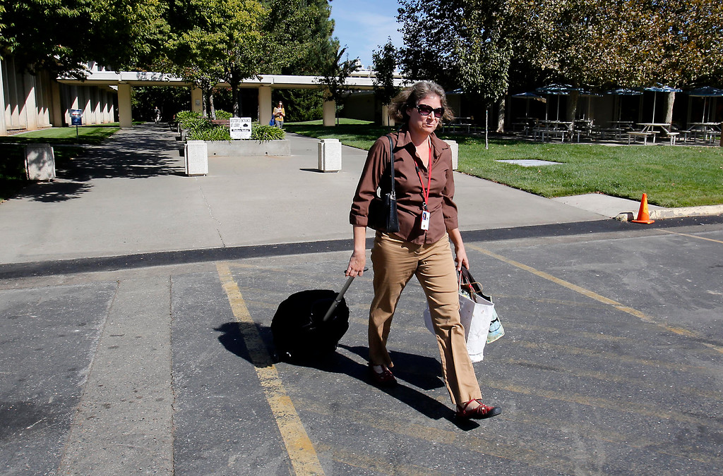 . With her rolling backpack and bags in hand, Bronwyn Hogan, an employee of the U.S. Fish and Wildlife Service, leaves the federal offices in Sacramento, Calif., Tuesday, Oct. 1, 2013.  Hogan and other federal employees were forced to go on furlough due to the partial federal government  shutdown.(AP Photo/Rich Pedroncelli)