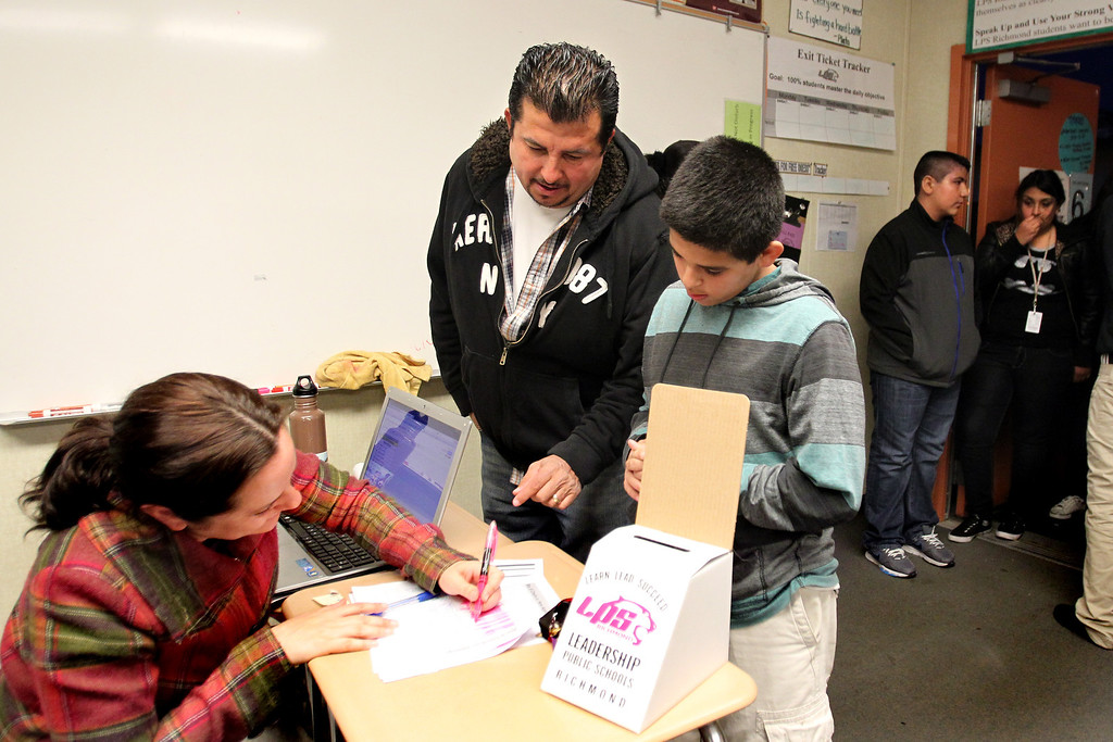 . School manager Ximena Montes, left, checks in Fernando Cervantes,13, as his father Alfredo looks on with hopes to be enrolled in Richmond Leadership Public High School through a lottery process in Richmond., Calif., on Thursday, Feb. 28, 2013.  The charter school registered 250 students but only 120 were accepted, including 50 of them because they have siblings currently enrolled.  (Ray Chavez/Staff)