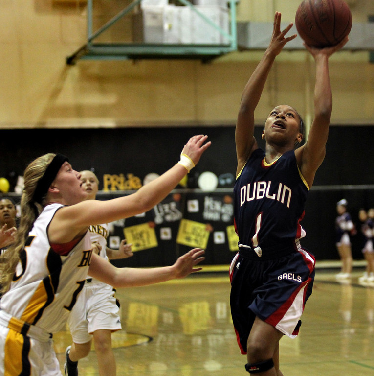 . Dublin\'s Milan Moses (1) drives through the hoop in front of Alameda\'s Maddy Lewis (15) in the first half of a North Coast Section Division II quarterfinal playoff game at Alameda High in Alameda, Calif., on Friday, Feb. 22, 2013.  (Ray Chavez/Staff)