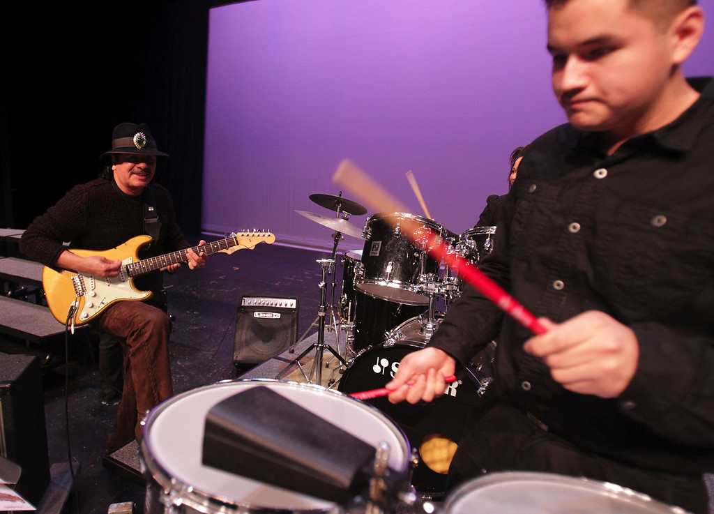 . Carlos Santana,from left, and San Leandro High School jazz band member Emmanuel Padillo, 17, play during an impromptu performance at the school in San Leandro, Calif., on Wednesday, Jan. 9, 2013. (Anda Chu/Staff)