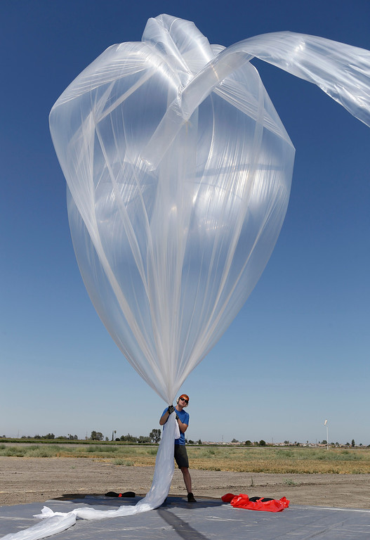 . T.J. Tierney holds the high-altitude balloon carrying electronic testing equipment steady as it fills with helium before being launched into the skies above Dos Palos, Calif. on Friday, July 26, 2013. Tierney is one of the launch commanders from Google\'s Project Loon. The test launch is part of the research being done by  the Google X division to create a high-altitude transponder network that will provide internet access to underserved areas of the world.  (Gary Reyes/Bay Area News Group)