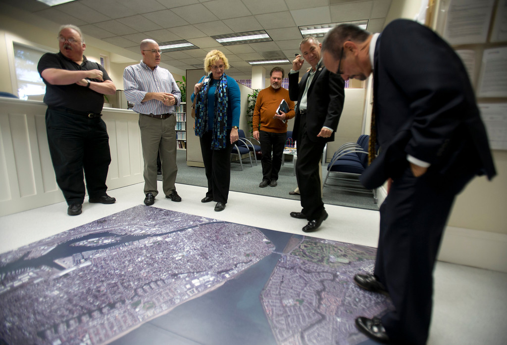 . Visitors inspect the aerial photo of the city of Alameda, Calif., at the newly remodeled Permit Center inside City Hall, Wednesday, Nov. 6, 2013 in Alameda. (D. Ross Cameron/Bay Area News Group)