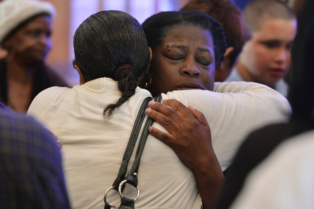 . Dinyal New, mother of slain teenager Lee Weathersby III, receives one of many hugs following a memorial service for her son held at Alliance Academy in Oakland, Calif. on Wednesday, Jan. 8, 2014. (Kristopher Skinner/Bay Area News Group)