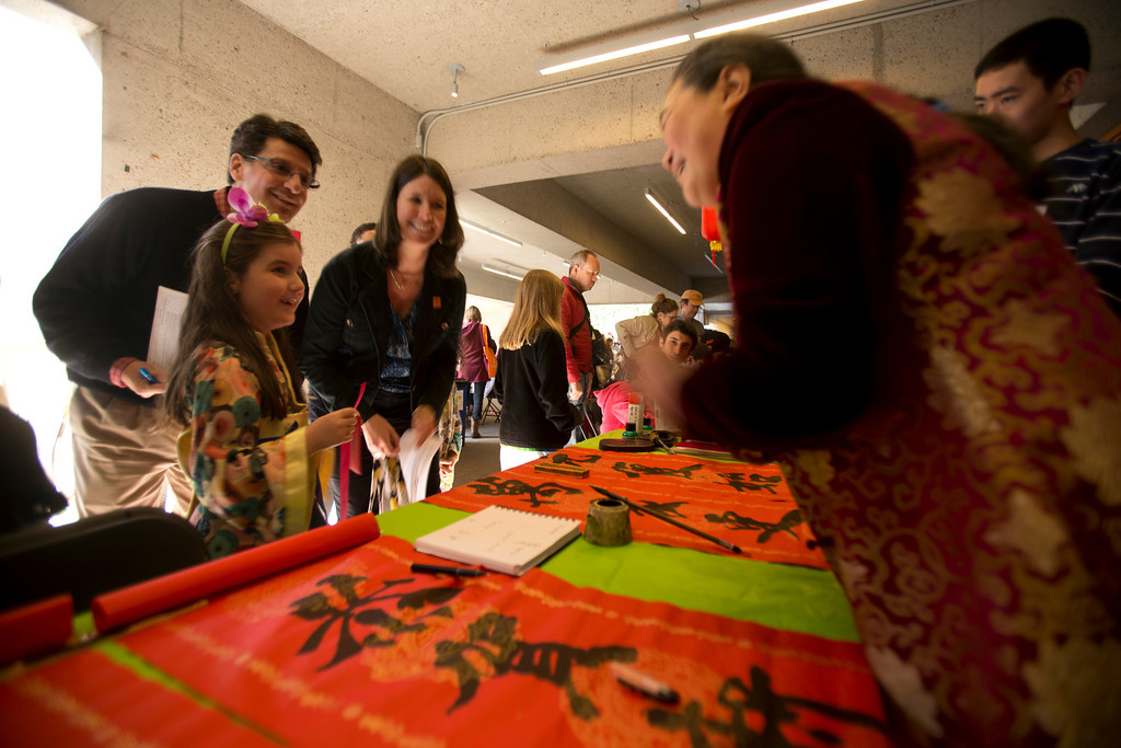 . Calligrapher Aiquin Zhou of El Cerrito, Calif., right, transliterates the name Grace Naclerio of Alameda, Calif., 7, into Chinese characters, much to the delight of Grace\'s parents Matt and Susan Naclerio, during the Oakland Museum of California\'s Lunar New Year celebration, Sunday, Feb. 17, 2013 in Oakland, Calif. (D. Ross Cameron/Staff)