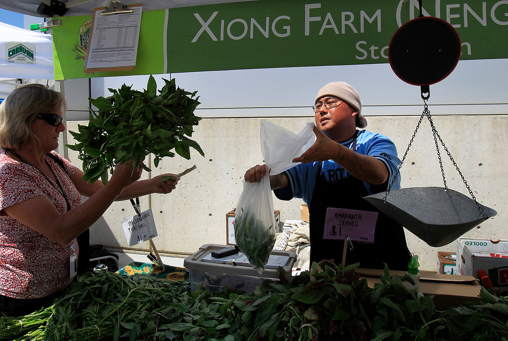 . From left, Bonnie Broderick buys some vegetables from Josh Her of Stockton\'s Xiong Farm, at the new Santa Clara Valley Medical Center Farmer\'s Market in San Jose, Calif. on Wednesday, May 15, 2013.  (LiPo Ching/Bay Area News Group)