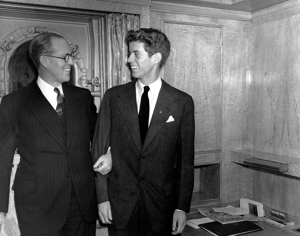 """. In this Jan. 5, 1938 file photo, Joseph P. Kennedy, left, U.S. Ambassador to Great Britain, stands with his son, John F. Kennedy, in New York. Kennedy, born in 1917, was the second son, and one of nine children, of business tycoon Joseph P. Kennedy. When first son Joseph Jr. was killed during World War II, Jack became the designated heir. Himself a Navy veteran and survivor of a collision with a Japanese destroyer, he would write to his friend Paul Fay that, once the war was over, \""""I\'ll be back here with Dad trying to parlay a lost PT boat and a bad back into a political advantage.\"""" (AP Photo)"""