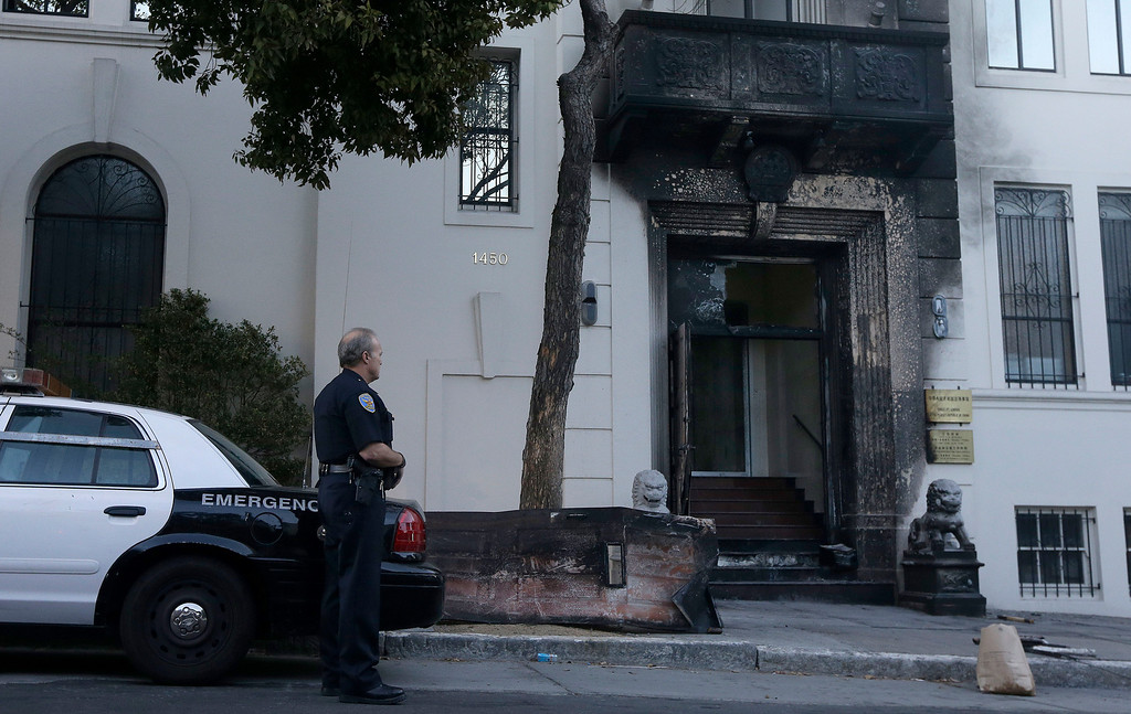 . A San Francisco Police officer stands outside of the damaged entrance to the Chinese Consulate in San Francisco on Thursday, Jan. 2, 2014. The consulate said in a notice on its website that a person came out of a van parked outside the compound Wednesday night with two buckets of gasoline, poured the fuel on the front of the consulate building and set it on fire. (AP Photo/Jeff Chiu)
