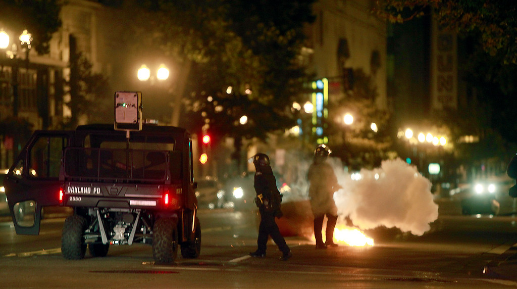 . Police extinguish a garbage fire on Broadway on the third day of protests  over the acquittal of George Zimmerman Monday evening, July 15, 2013 in Oakland, Calif. (Karl Mondon/Bay Area News Group)