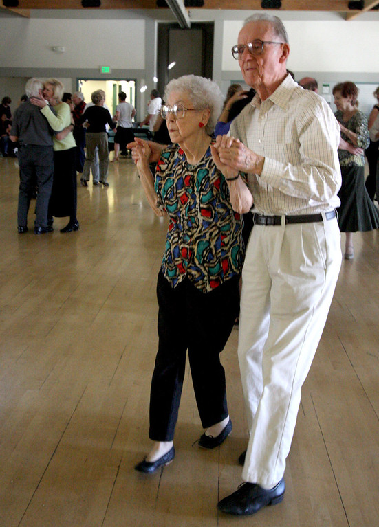 . Betty Beebe, left, and Bille Andersen, both of Livermore, dance to the music of the Cool Tones with lead singer, Kathy Blackburn, at the Pleasanton Senior Center\'s 20th anniversary celebration tea dance in Pleasanton, Calif. on Sunday, March 3, 2013.  (Jim Stevens/Staff)