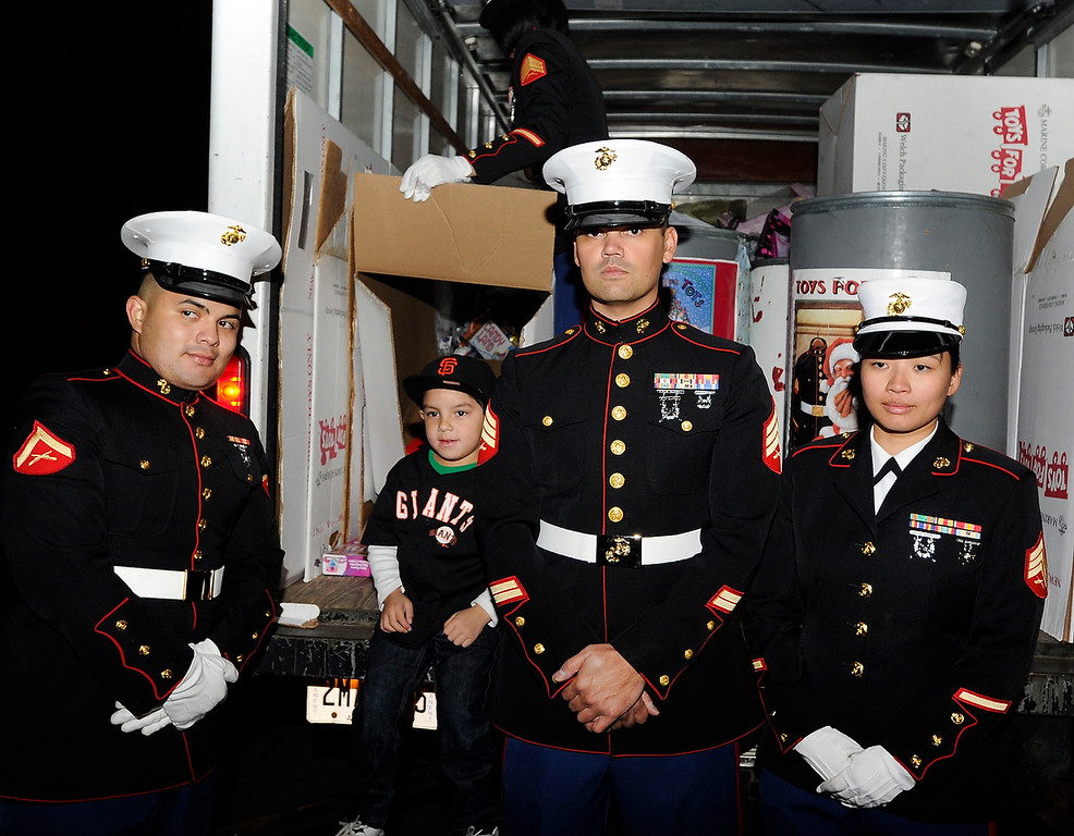 . While other Giants fans wanted their photo made with reliever Sergio Romo, young Jaeden Burgstaller, 4, of Martinez, second from left, asked to be photographed with members of the Marine Corps Reserve Toys For Tots at Kinders Meat and Deli on Wednesday, Dec. 12,  2012, in Pleasant Hill, Calif.  Kathy Lucero, who took grandson Jaede to see the World Champion Giant, said the young boy was more interested in the folks who were packing away all the toys for the children at the event. Romo teamed up with rapper E-40 and Marine Corps Reserve Toys for Tots collecting a toy in exchange for an autograph with the two celebrities. This 16-foot truck and an 8-pack van were filled with toys at the end of the event, according to Staff Sgt. Erick Bannar. (Susan Tripp Pollard/Staff)