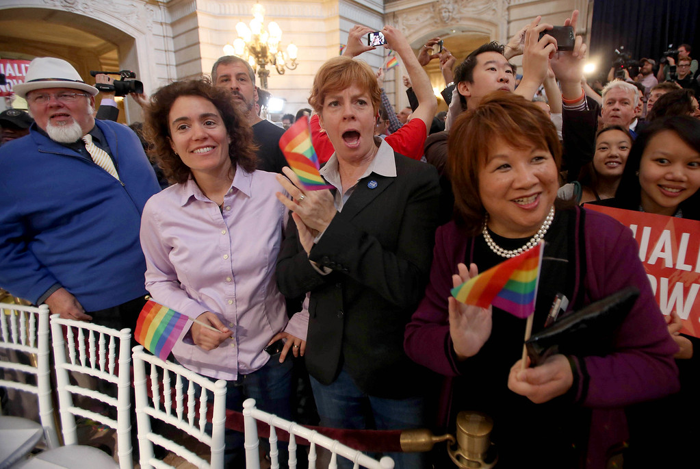". Zoe Dunning, center, and her partner Pam Grey, of San Francisco, along with Mary Jung, right, celebrate at City Hall in San Francisco, Calif., on Wednesday, June 26, 2013. Dunning is vice-chair of the San Francisco Democratic party and a former military officer who crusaded against the ""Don\'t Ask, Don\'t Tell\"" policy. The U.S. Supreme Court dismissed California\'s Proposition 8 and declared the 1996 Defense of Marriage Act unconstitutional. (Jane Tyska/Bay Area News Group)"