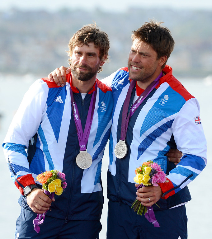 ". File -This August 5, 2012 file photo shows Britain\'s Andrew Simpson (R) and Iain Percy celebrating on the podium after winning the silver medal in the Star sailing class at the London 2012 Olympic Games in Weymouth, England. A sailor killed when a Swedish catamaran capzied May 9, 2013 while training for the upcoming America\'s Cup races was identified as Olympic medal-winning Briton Andrew ""Bart\"" Simpson.  \""It is with immense sadness that Artemis Racing confirms the tragic death of crewmember,\"" said a statement on the America\'s Cup website, after the accident during training in San Francisco Bay.  \""Simpson ... was one of the 11-man crew aboard Artemis Racing\'s AC72 catamaran which capsized during training on San Francisco Bay ahead of this summer\'s America\'s Cup.  It said he was \""trapped underneath the boat and despite attempts to revive him, by doctors afloat and subsequently ashore, his life was lost,\"" adding that all other crewmembers were accounted for.   \""The entire Artemis Racing team is devastated by what happened,\"" said Artemis Racing chief executive Paul Cayard. \""Our heartfelt condolences are with Andrew\'s wife and family.\""   AFP PHOTO / Files / William WESTWILLIAM WEST/AFP/Getty Images"
