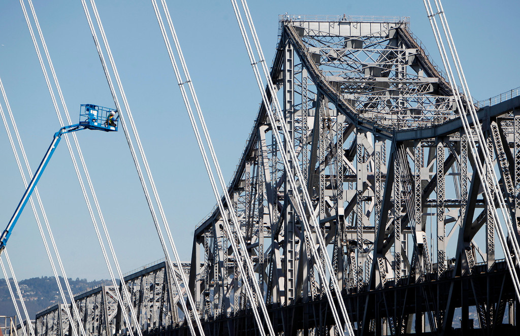 . Against the backdrop of the old 1936 cantilever truss span, an ironworker focuses on a suspender rope of the new eastern span of the Bay Bridge on March 1, 2013. (Karl Mondon/Bay Area News Group)