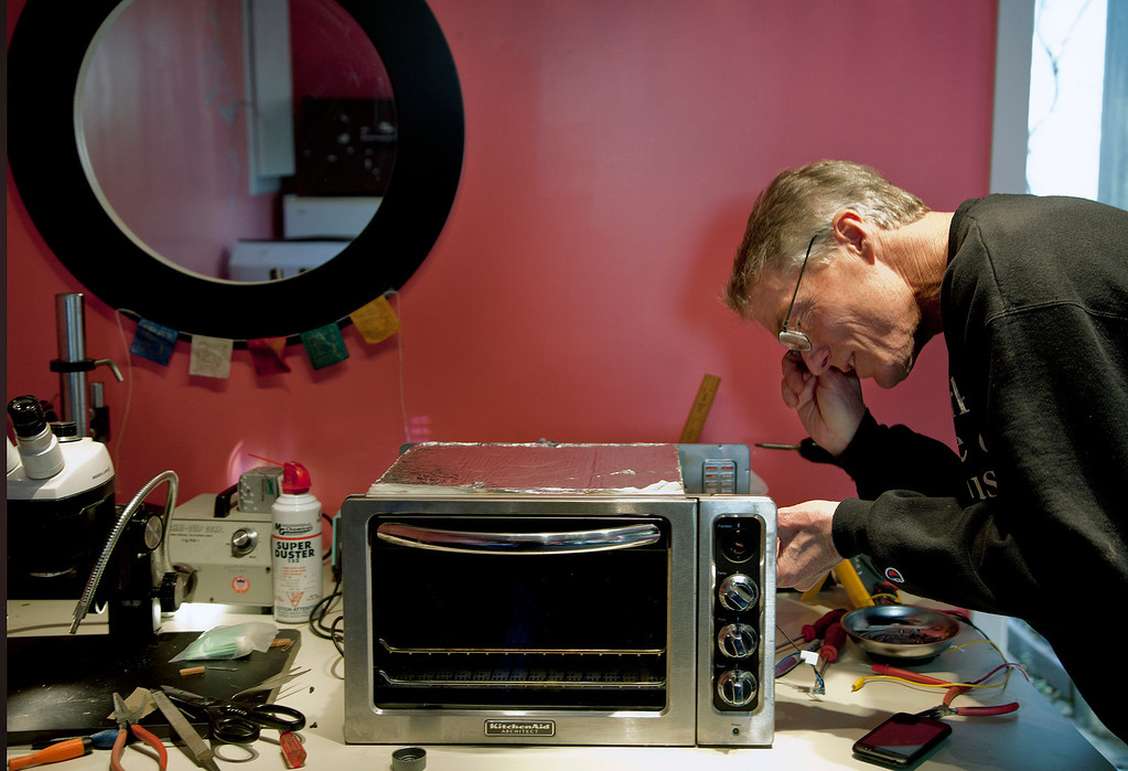 . John Eaton replaces the function dial of a neighbor\'s toaster oven after repairing it at his home in Palo Alto, Calif. on Friday, Feb. 15, 2013.   (LiPo Ching/Staff)