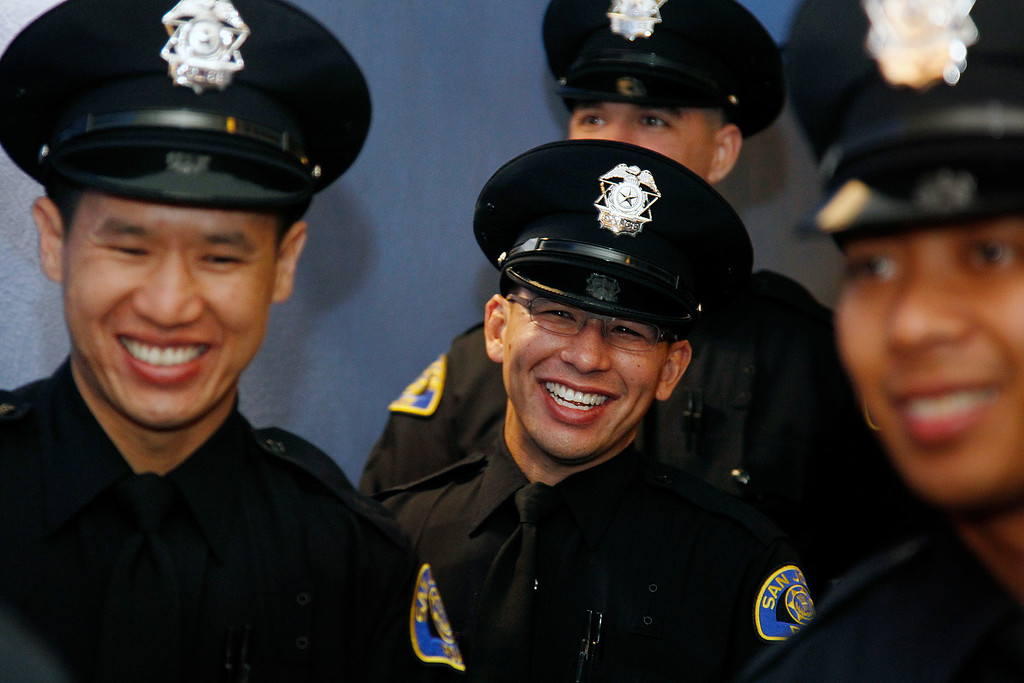 . At center, San Jose Police Department Recruit Officer Alex Ribeiro waits with fellow Officers in the procession line at the San Jose Police Academy graduation in San Jose, Calif. on Friday, March 15, 2013.   (LiPo Ching/Staff)