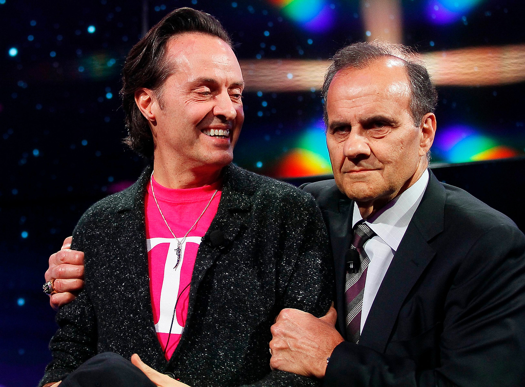 . John Legere (L), CEO of T-Mobile USA, is hugged by former New York Yankees MLB baseball manager Joe Torre during a news event at the Consumer Electronics Show (CES) in Las Vegas January 8, 2013. (REUTERS/Rick Wilking)