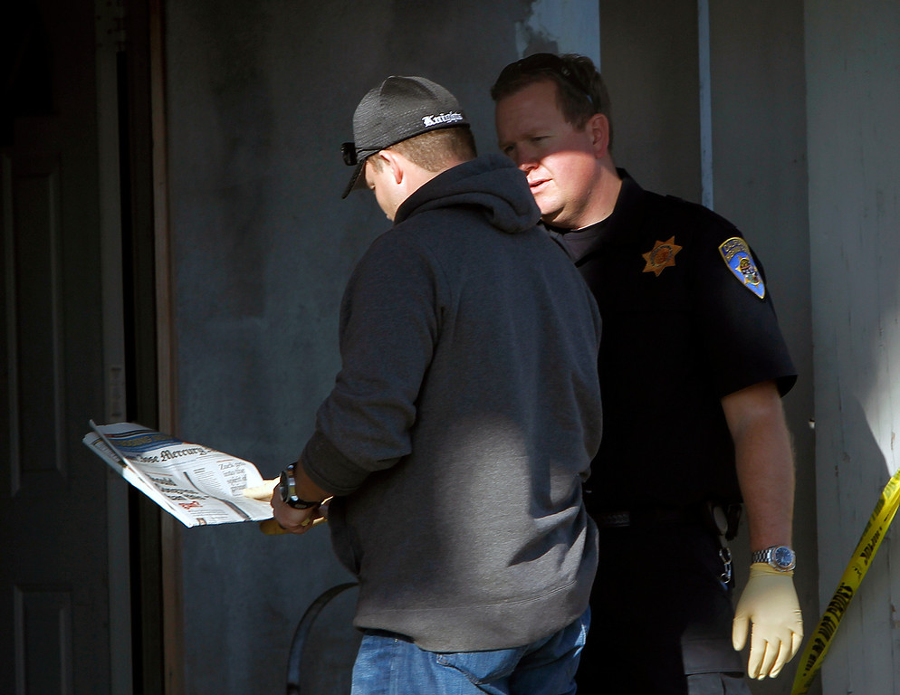 . At right, a California Highway Patrol officer displays a newspaper featuring a gun control article at Everett Basham\'s house on Humbolt Ave., in Santa Clara, Calif. on Wednesday, Feb. 13, 2013.   (LiPo Ching/Staff)