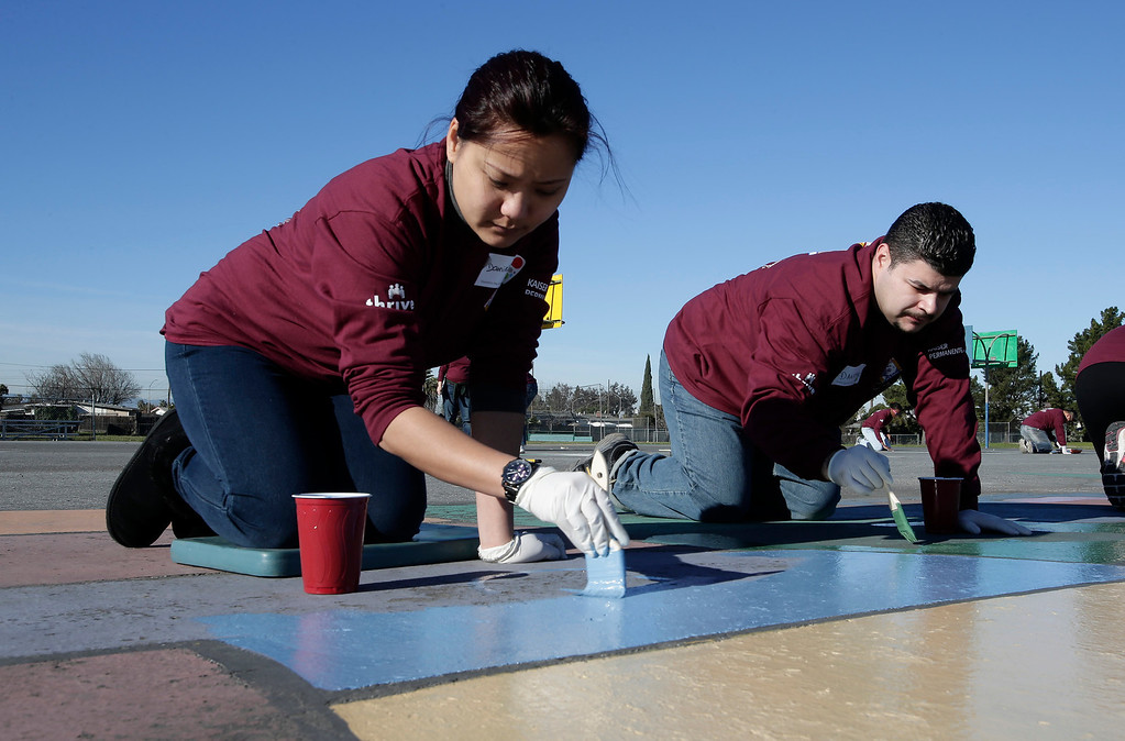. Kaiser Permanente volunteers, Danielle Tai and Daniel Arellano, repaint the playground at Ryan Elementary School during a Dr. Martin Luther King Jr. day-of-service activity in San Jose, Calif. on Monday, January 21, 2013.   (Gary Reyes/ Staff)