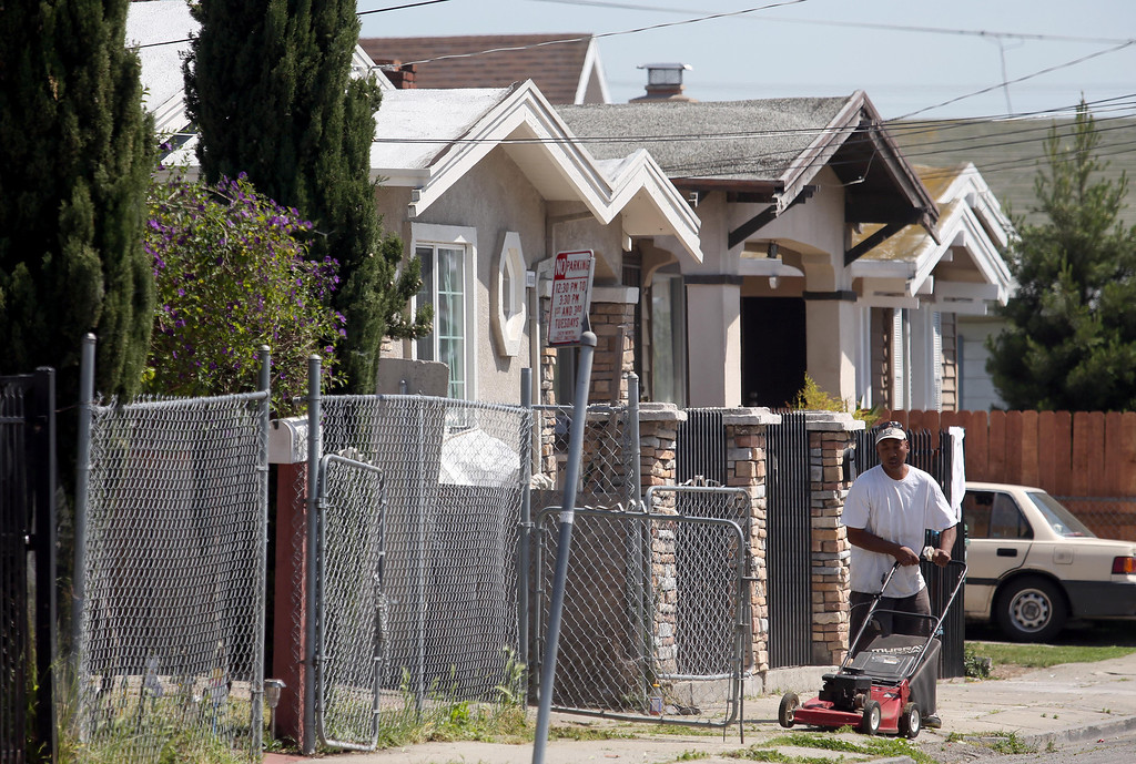 . Longtime East Oakland resident Paris Moore, 52, mows a neighbor\'s lawn on Holway Street in Oakland, Calif., on Friday, April 12, 2013.  (Jane Tyska/Staff)