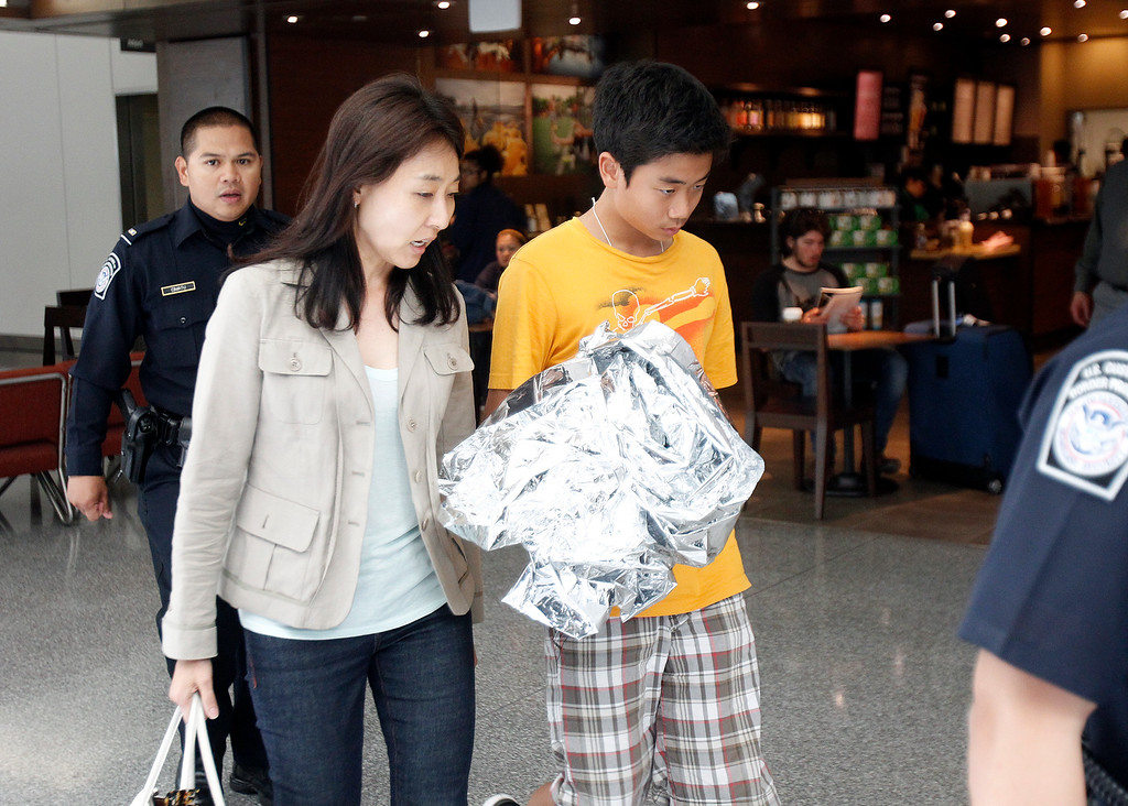 . Unidentified people exit the Reflection Room and were escorted to the terminal boarding area after an Asiana Airlines  Boeing 777 arriving from Seoul, South Korea, crashed at the San Francisco International Airport, in San Francisco, Calif. on Saturday July 6, 2013.  Reportedly friends and family of the passengers were staying in the Reflection Room while waiting to see their family.  (LiPo Ching /Bay Area News Group)
