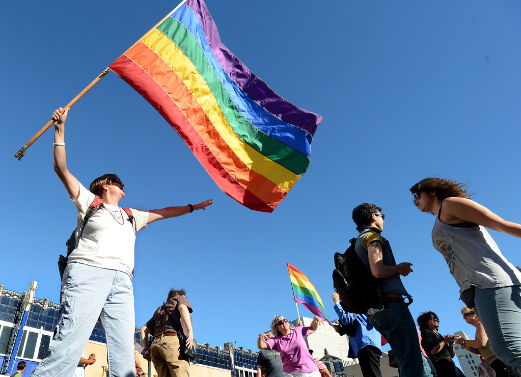 . Lois Bukowski, of Oakland, waves a rainbow flag, a symbol of gay pride, as she and others dance during a celebration of the Supreme Court\'s decision on Proposition 8 and the Defense of Marriage Act during an event held in Oakland, Calif., on Wednesday, June 26, 2013. The U.S. Supreme Court dismissed California\'s Proposition 8 and declared the 1996 Defense of Marriage Act unconstitutional. (Doug Duran/Bay Area News Group)