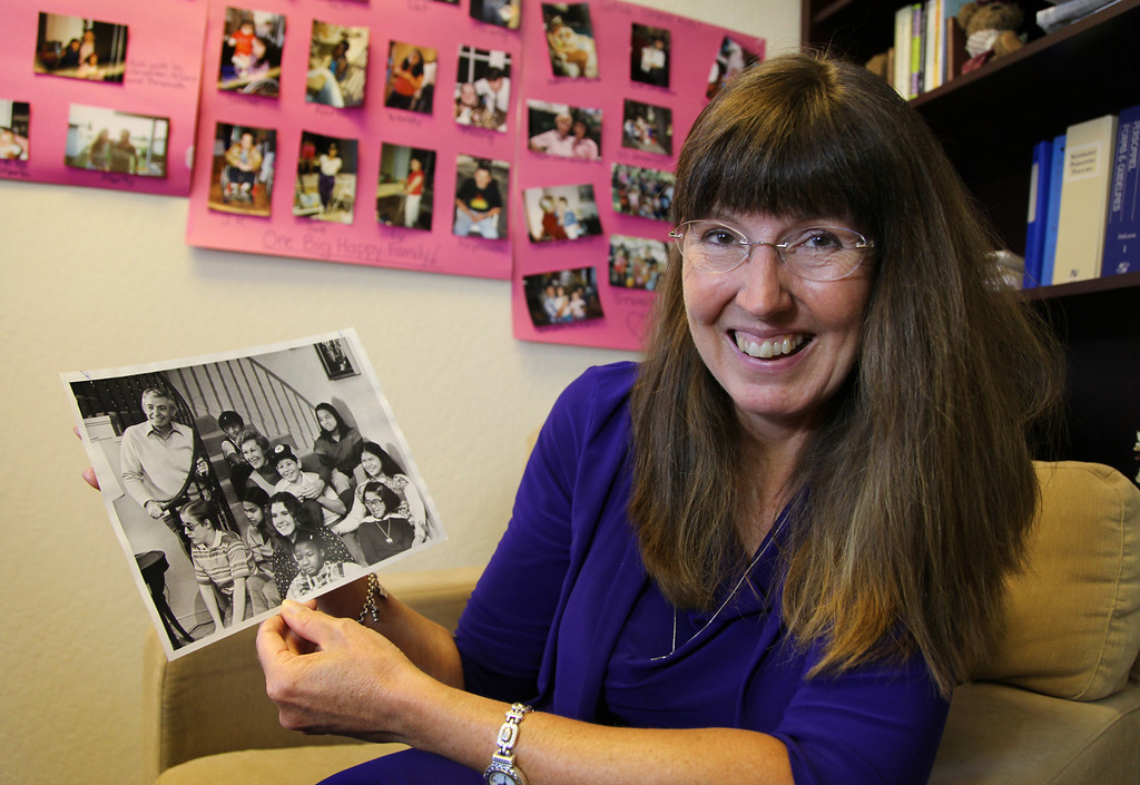 . Doni DeBolt, executive director of AASK (Adopt A Special Kid), holds a photo of her large family of 20 from 1970 at the AASK office in Oakland, Calif., on Wednesday, June 19, 2013. (Laura A. Oda/Bay Area News Group)