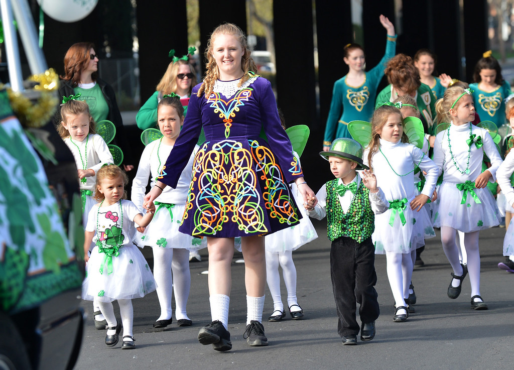 . Alexandra Brain, of Castro Valley, holds the hands of kids from Powell\'s Irish Dancers as the walk down Dublin Boulevard during the Saint Patrick\'s Day Parade in Dublin, Calif., on Saturday, March 16, 2013. (Dan Rosenstrauch/Staff)