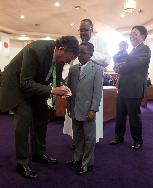 . California State University Chancellor Timothy White, left, gives his business card to 11-year-old Marcus Williams of Union City, Calif. while Bishop J.W. Macklin and CSU-East Bay President Leroy Morishita watch at Glad Tidings Church of God during a service at the church, Sunday, March 10, 2013 in Hayward, Calif. White visited the church as part of the annual Super Sunday event to encourage African Americans to attend college. Marcus stepped up when the bishop asked who among his congregation might step up to replace White as chancellor someday. (D. Ross Cameron/Staff)